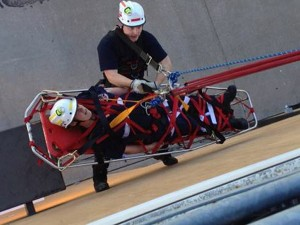 During a ROCO training scenario, a Hazelwood firefighter repels himself down the side of a building to rescue a simulated victim.  He makes sure the victim is secured in the rescue basket and guides it up while being hoisted to the building's rooftop.
