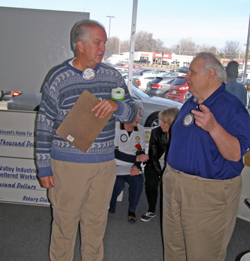 Florissant License office manager Wayne Williams (right) talks to a fellow Rotarian at Saturday's rally. Williams said they're  awaiting word from the state  of Missouri on the whether  It would reverse its decision on awarding the office  to a  St. Charles County company.