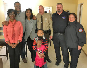 The Bell family, from left: Linda, Jason, Dorothy, Justin and Jasmine with St. Louis County Officer Bob Rinck and Christian Hospital EMS paramedics Jeremy Bell and Tricia O'Laughlin.