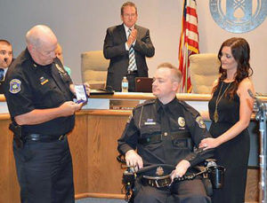 Officer Craig Tudor, with his wife, accepting the Purple Heart award, given by Police Chief Gregg Hall.