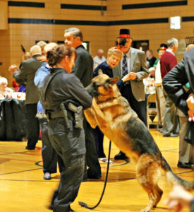 """Eddie the Florissant Police Dog. was a big hit in his little top hat, and kindly meandered around the party to pose for photos and wish everyone a Happy New Year. He even took his """"mom,"""" Officer Lori Mahn, for a spin."""